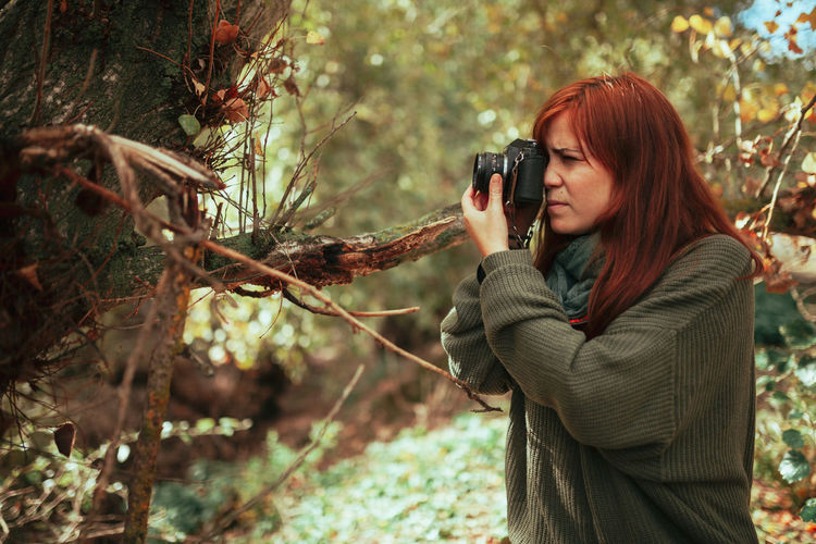 Young woman photographing with camera while standing in forest