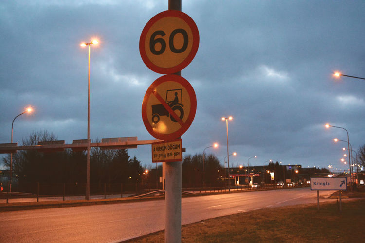 Road sign by street light against sky
