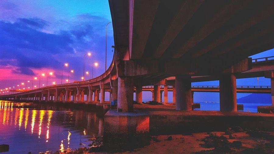 Illuminated bridge over river against sky