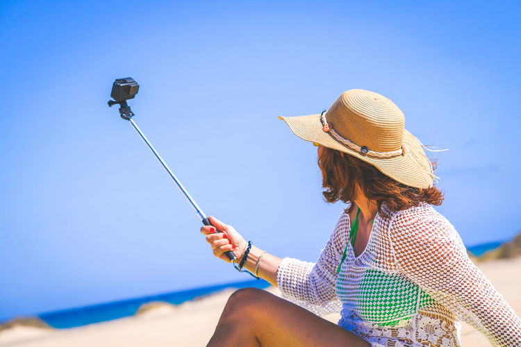 Trendy tourist doing a video with action cam on an amazing tropical beach during vacation Beautiful woman with straw hat make social story sitting on white sand Travel and new trend technology concept 40s 50s Addicted Aunique Beach Bikini Blue Canary Communicate Communication Cute Day Off Fashion Female Friends Fun Girl Hand Happy Holiday Internet Island Leisure Lifestyle Media Middle Millenial Multimedia Nature Network Ocean One Online  Outdoor People person Relaxation Sea Sharing  Smart SPAIN Stories Summer Sun Swimsuit Unique Using Weverywhere Wireless