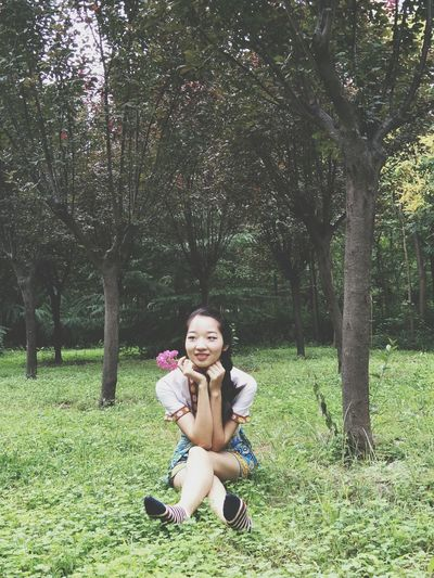 Smiling young woman sitting in park