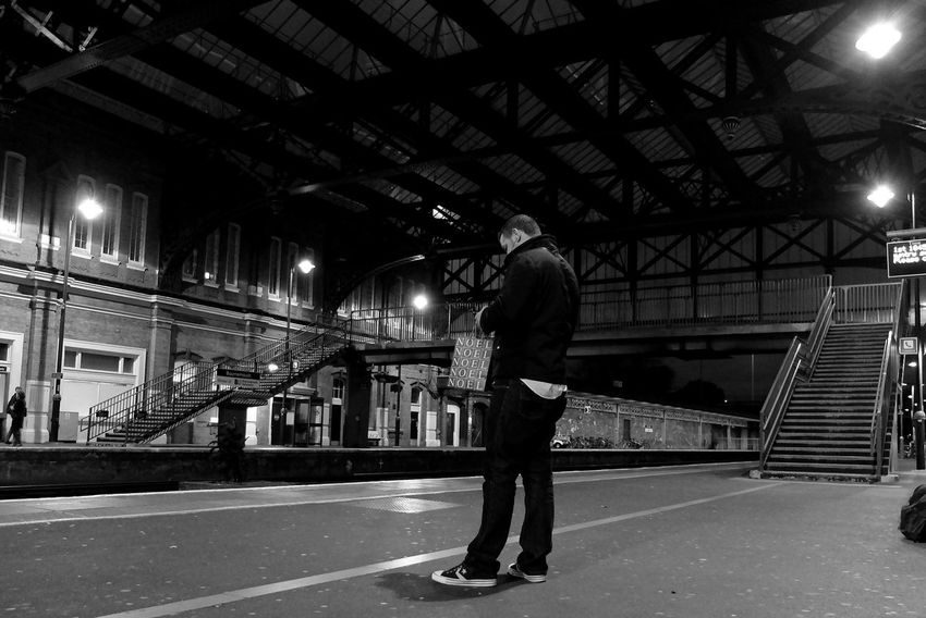 Texting while waiting for a train on platform 2 at Bournemouth Central Station. Train Station After Dark Black & White Dorset