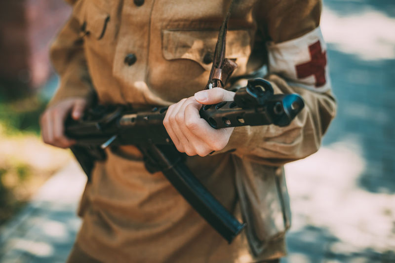 Unidentified woman reconstructor dressed as a Soviet military nurse with a submachine gun in hand. Close up on hands Weapon Gun Ww2 WWII Ww1 War Soviet Soldier Ussr Army Millitary Uniform Reconstructor Submachine Unidentified