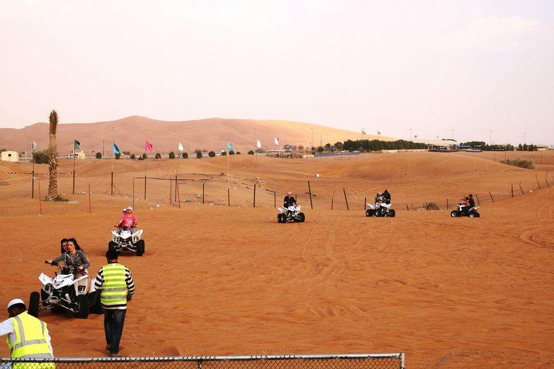 People riding quadbikes at desert against sky