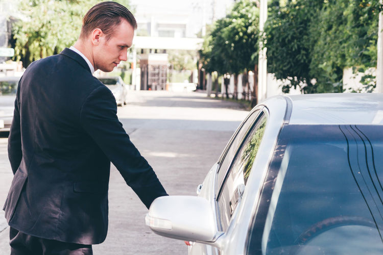 Businessman opening car door