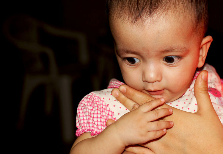 Cropped hand touching cute baby girl