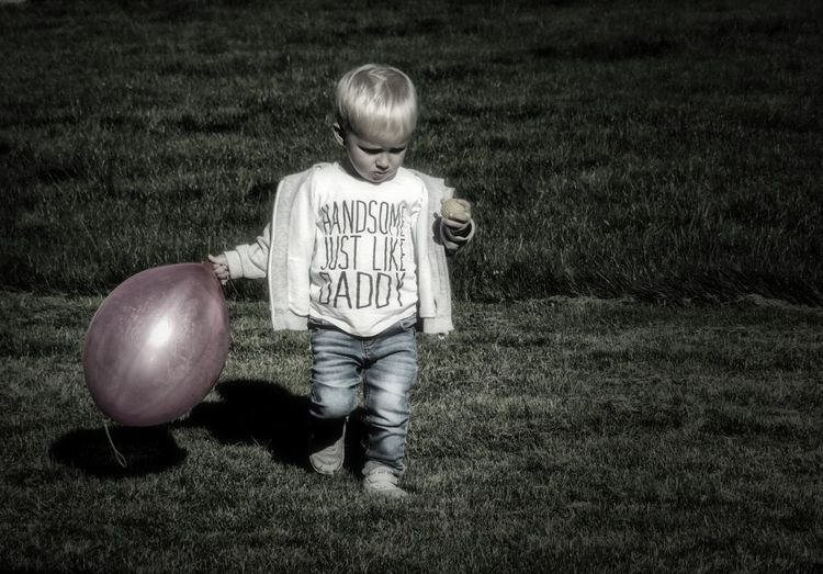 Full length of boy holding balloon while walking on grassy field at park