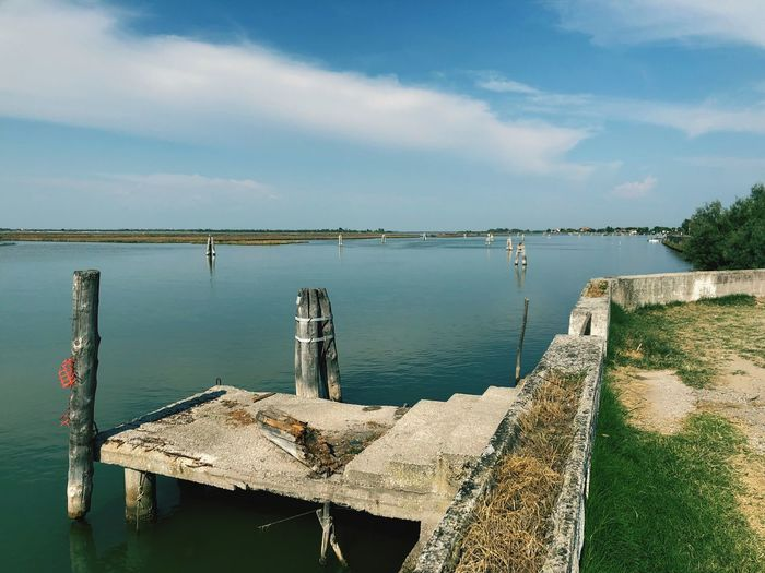 Pier on Venice Jesolo lido Italy Venice Lagoon Sea Canal Pier Water Sky Tranquility Sea Tranquil Scene Scenics - Nature Cloud - Sky Beauty In Nature Nature Day No People Sunlight Outdoors Post Land Beach Built Structure Wooden Post Non-urban Scene Idyllic