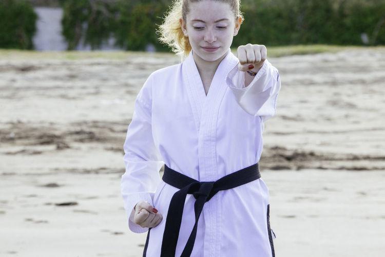 Teenage girl practicing martial arts at beach