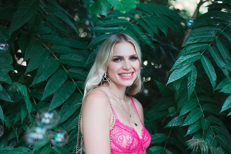 Portrait of smiling woman standing against plants