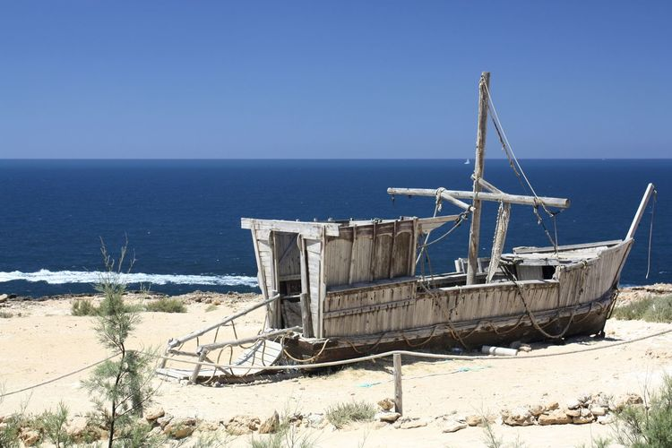 Boat on shore by calm blue sea against clear sky