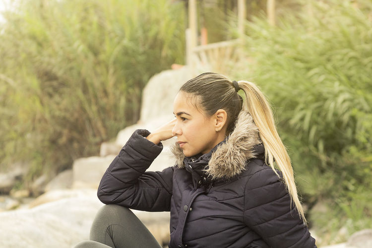 Portrait of beautiful young woman sitting outdoors