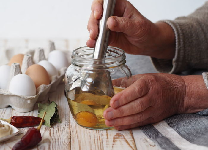 .an elderly woman prepares homemade mayonnaise in a jar with vegetable oil and an egg.