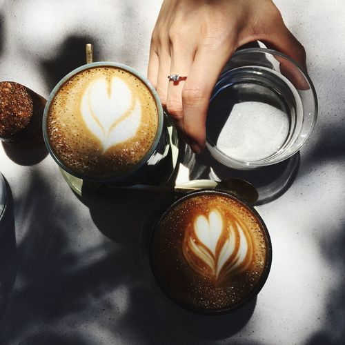 EyeEm Selects Coffee - Drink Coffee Cup Drink Refreshment Food And Drink Frothy Drink Cappuccino Froth Art Table No People Monochrome Outdoors Human Hand Human Body Part High Angle View One Person Saucer Real People Freshness Close-up Directly Above Hand Glass Cafe