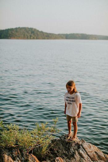 Boy standing in lake against sky