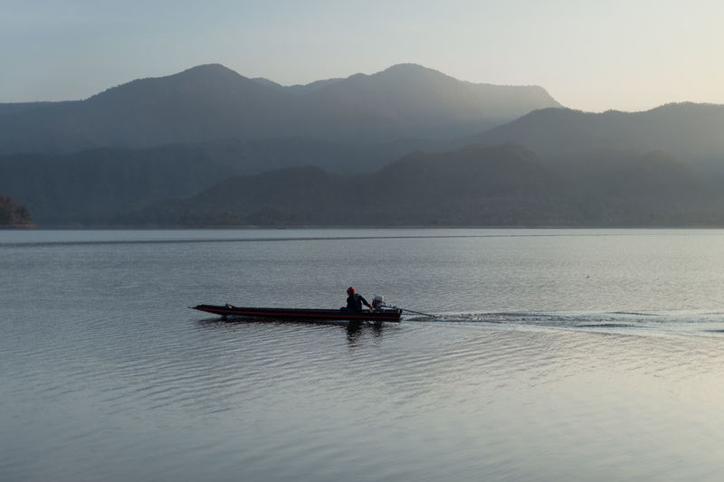 Nautical Vessel Mountain Water Transportation Mode Of Transportation Waterfront Beauty In Nature Scenics - Nature Mountain Range Tranquil Scene Tranquility Sky Nature Real People Rowing Non-urban Scene Lake Day One Person Outdoors Rowboat Fisherman