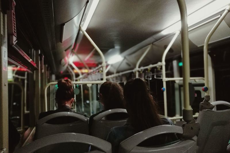Rear view of women traveling in bus at night