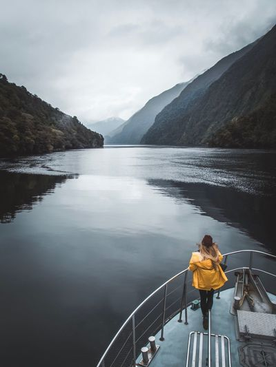Hey Sailor! #doubtfulsound #newzealand#nzmustdo#destinationnz#openmyworld #goplayoutside#greatnorthcollective #wildernessculture#letsgosomewhere #ourplanetdaily#wildlifeplanet #keepitwild #stayandwander#campvibes #lonelyplanet #passionpassport#themountainiscalling #theoutbound#mind #nzmustdo #newzealand#nz #destinationnz #special_shots#jaw_dropping_shots #depthsofearth#sunset_vision #main_vision#watchthisinstagood#awesome_photographers#aroundtheworldpix #igrefined #mthrworld#beautifuldestinations #awesomeearth#places_wow #awesome_ea Water Mountain Railing One Person Rear View Sky Real People Beauty In Nature Leisure Activity Lake Scenics - Nature Transportation Cloud - Sky Nature Day Outdoors Lifestyles Looking At View Tranquility Mountain Range
