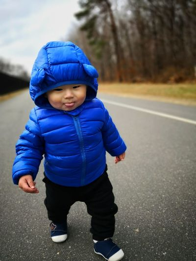Full length of cute baby boy wearing winter jacket while walking on road