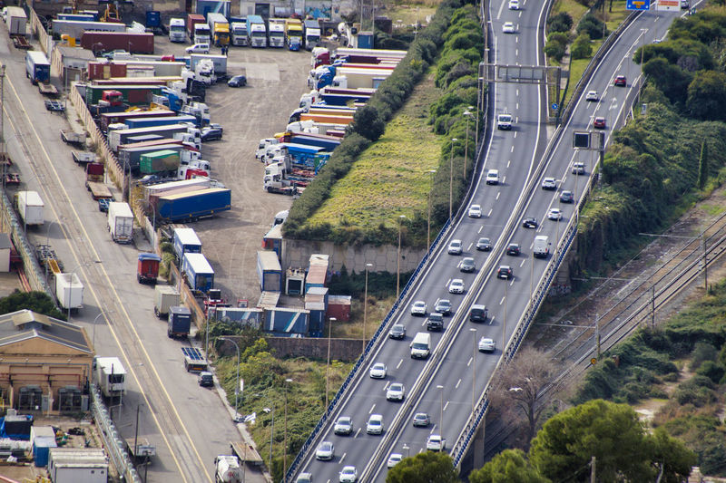 High angle view of traffic on city street and parked trucks with cargo container
