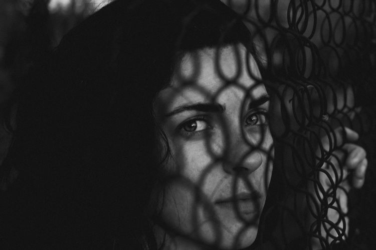Close-Up Portrait Of Young Woman By Fence