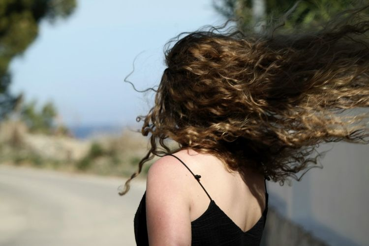 Rear View Of A Woman With Hair Tossed In Wind