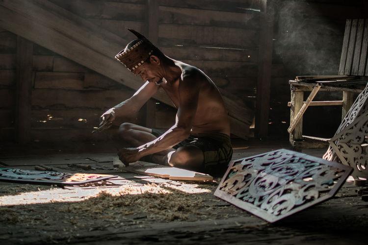 Talawang engraving artist. talawang is tradittional dayak shield