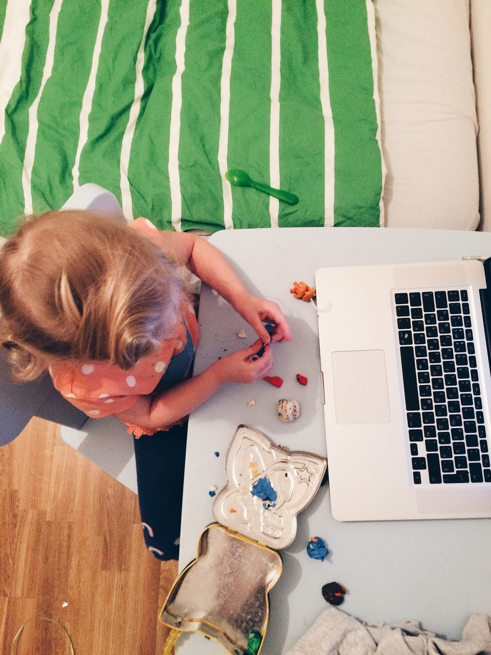 High Angle View Of Girl Playing With Clay While Sitting In Front Of Laptop At Home