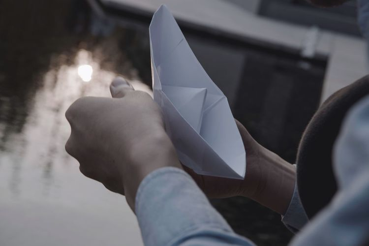 Close-up of woman holding paper boat