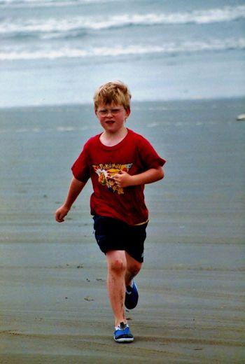 Boy running on sand against sea at beach