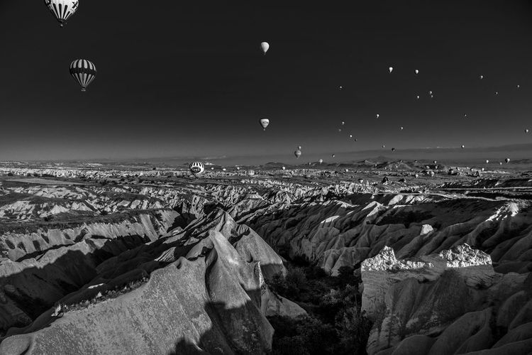 Hot air balloons over rocky mountains at cappadocia
