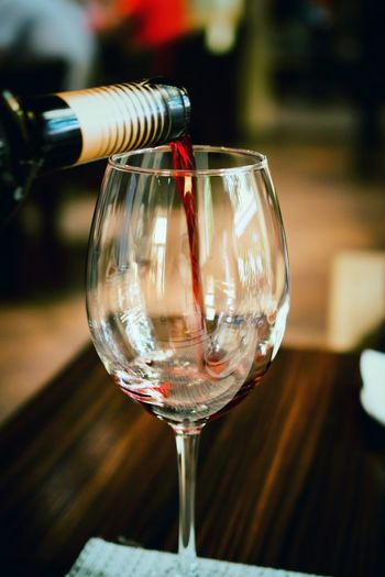 Close-up of red wine pouring in glass