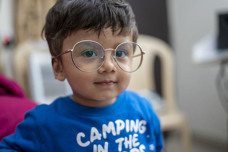 Close-up portrait of cute boy wearing eyeglasses at home