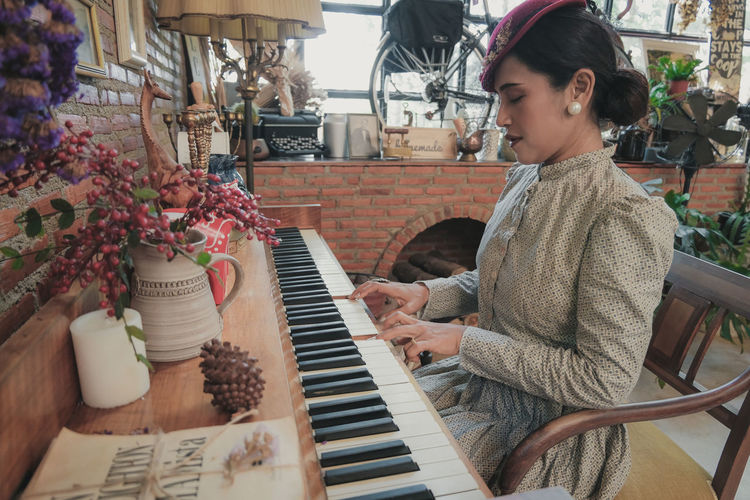 Woman playing piano while sitting at home