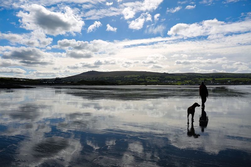 Silhouette man with dog walking on frozen lake against cloudy sky