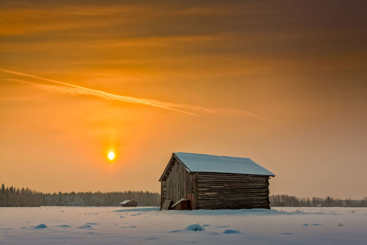 House against sky during winter at sunset
