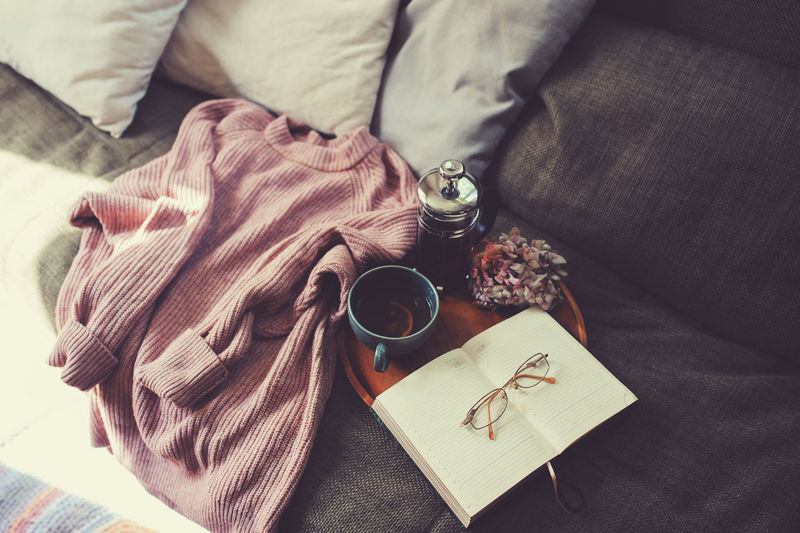 Indoors  Cup Furniture Drink Book Still Life Food And Drink Textile No People Couch Home Cozy Relaxing Winter Lazy Weekend Sweater Knitted Sweater Tea Read Glasses Notes Pillows