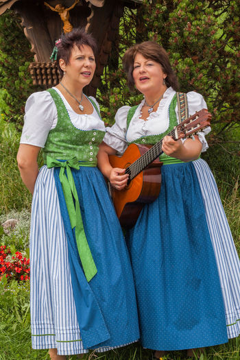 Two attractive middle-aged female German singers wearing traditional dirndls and playing a guitar at an outdoor festival or at the Oktoberfest, Country Living Arts Culture And Entertainment Bonding Casual Clothing Cheerful Day Enjoyment Friendship Front View Guitar Happiness Holding Leisure Activity Lifestyles Music Musical Instrument Musician Outdoors Playing Plucking An Instrument Smiling Standing Togetherness Two People Women