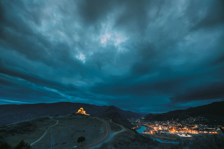 Aerial view of illuminated town by mountain against sky