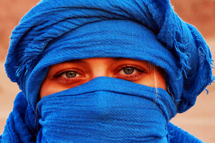 Close-up portrait of woman covered with blue scarf