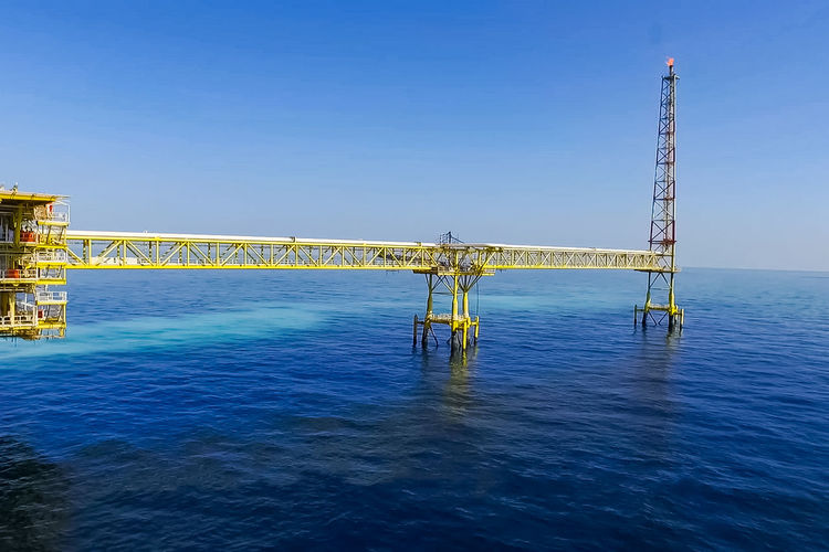 View of bridge over sea against clear blue sky