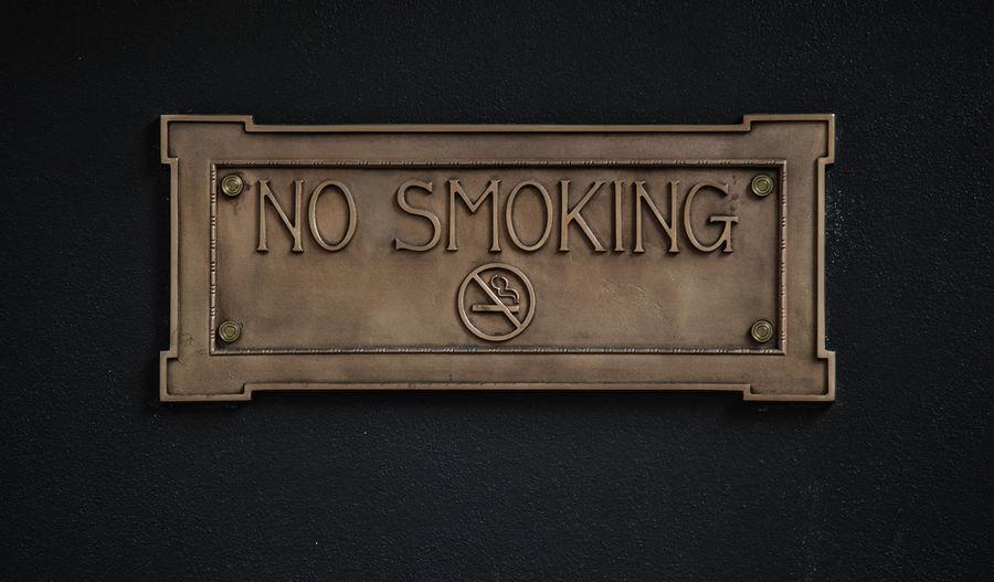 Close-up of no smoking sign on black wall