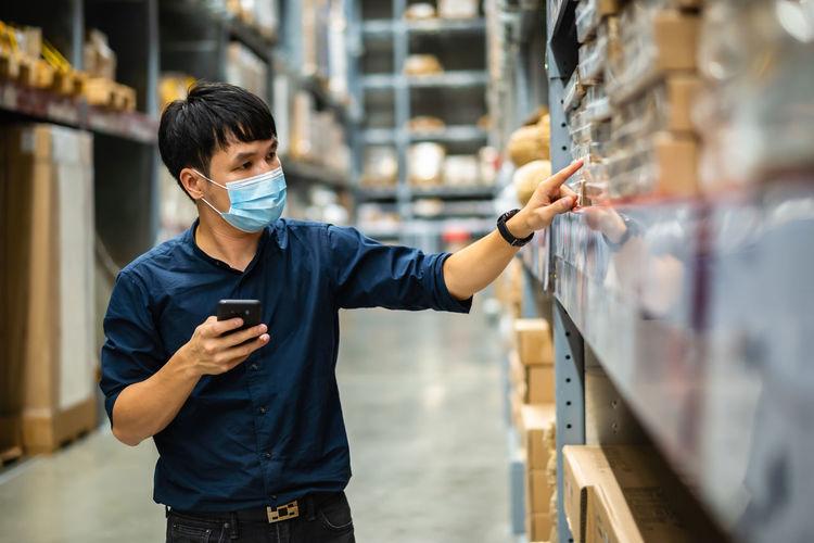 Man wearing mask working in warehouse