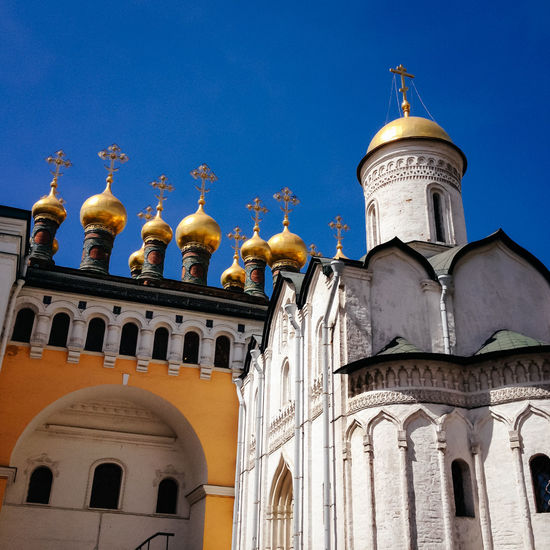 Golden domes of terem churches against clear blue sky