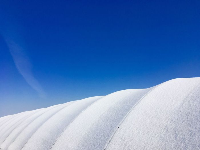 Low Angle View Of Snowy Field Against Clear Blue Sky