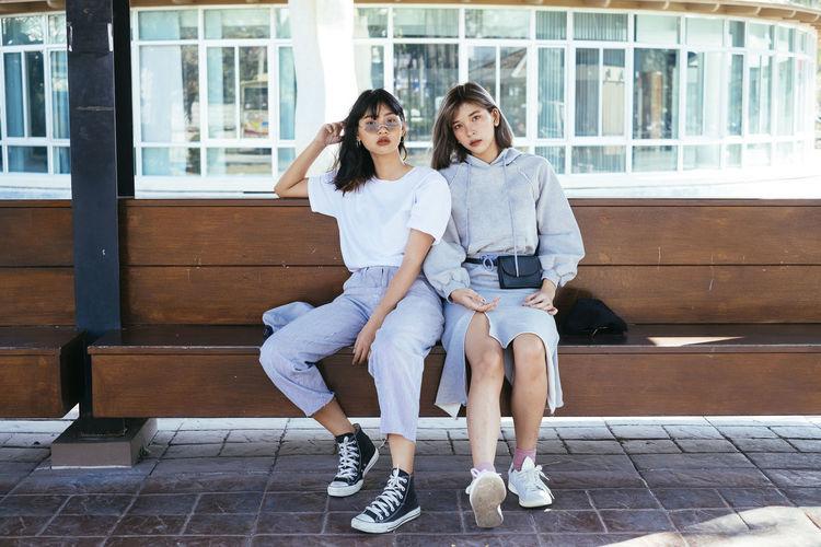 Portrait of friends sitting on bench
