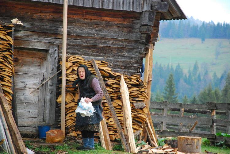 Senior woman standing by hut