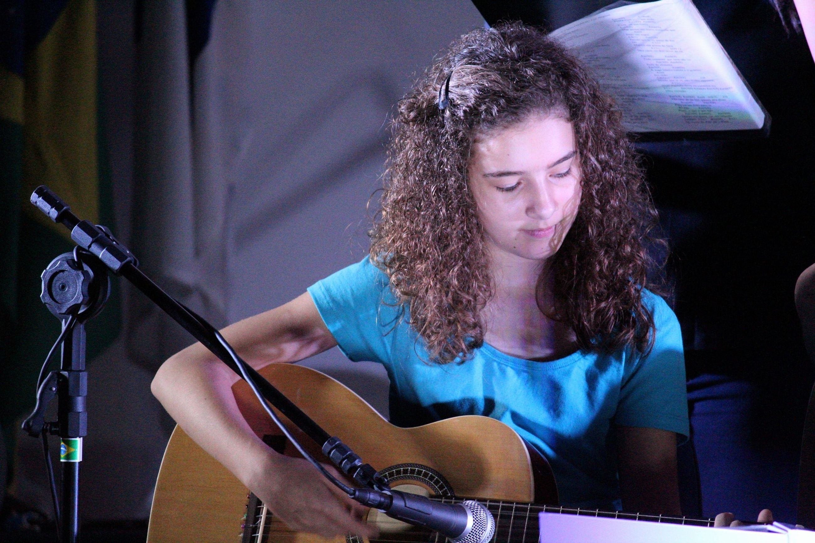 music, musical instrument, string instrument, arts culture and entertainment, musician, performance, artist, musical equipment, real people, one person, playing, front view, guitar, indoors, young adult, hairstyle, young women, input device, microphone, skill, hair, plucking an instrument, stage