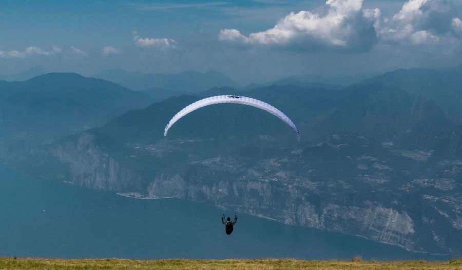 Man Paragliding Over Mountain Against Sky