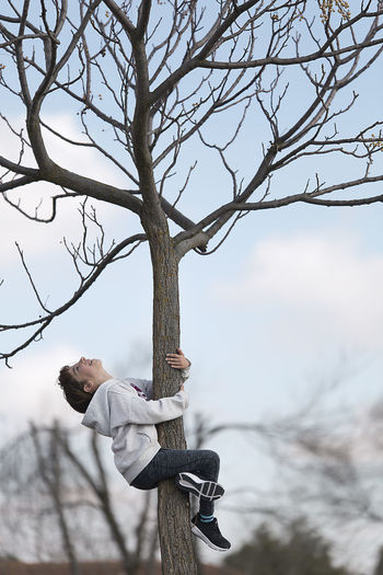 Ten-year-old girl climbing on a tree looking at the camera. Horizontal shot with natural light Bare Tree Branch Casual Clothing Climbing Day Full Length Girl Leisure Activity Lifestyles Nature One Girl Only One Person Outdoors People Real People Sky Tree Tree Trunk Young Adult